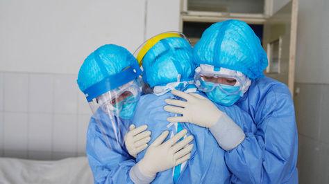La foto de AFP es del 28 de enero de 2020. Muestra a varios profesionales sanitarios abrazándose en una sala de aislamiento en un hospital en Zouping, en la provincia de Shandong, en el este de China.
